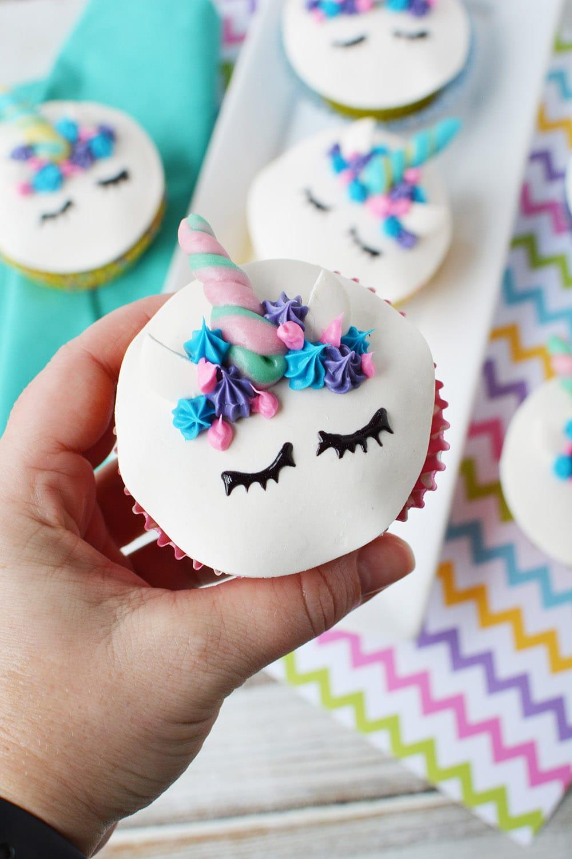 holding a cute unicorn face cupcake