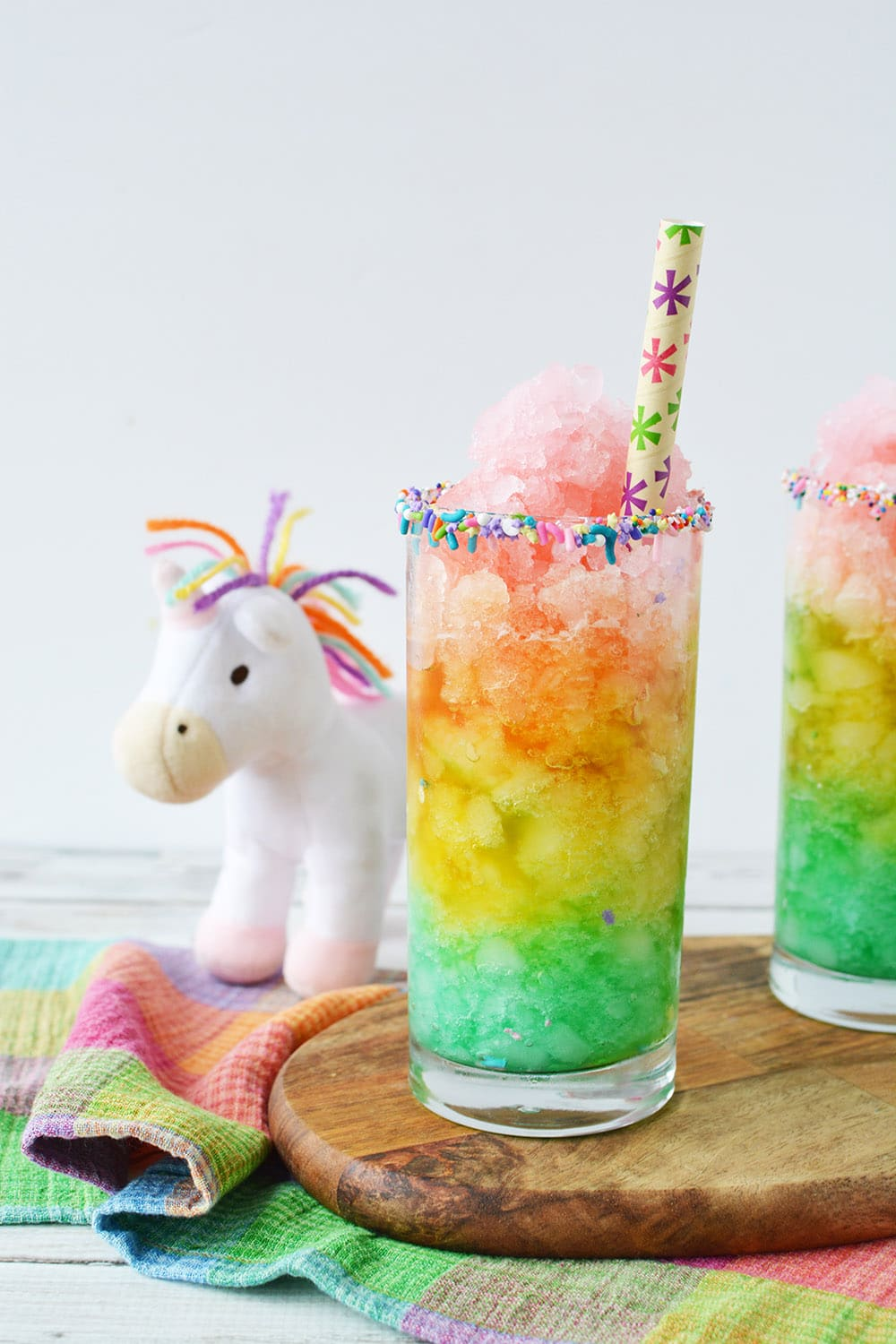 Rainbow slush next to a unicorn plush toy