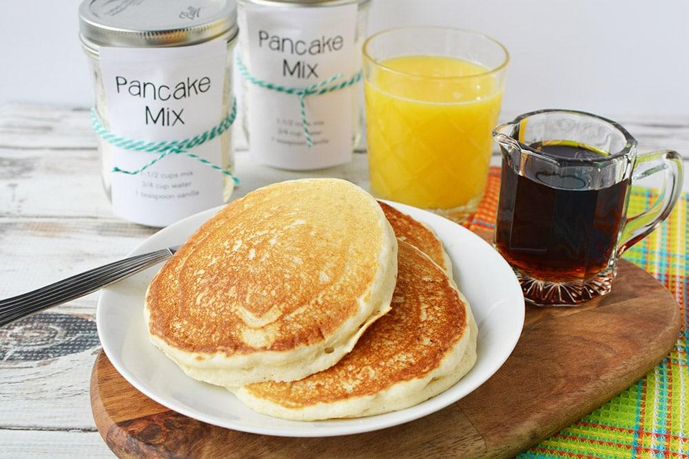 pancakes on plate with jars of homemade pancake mix