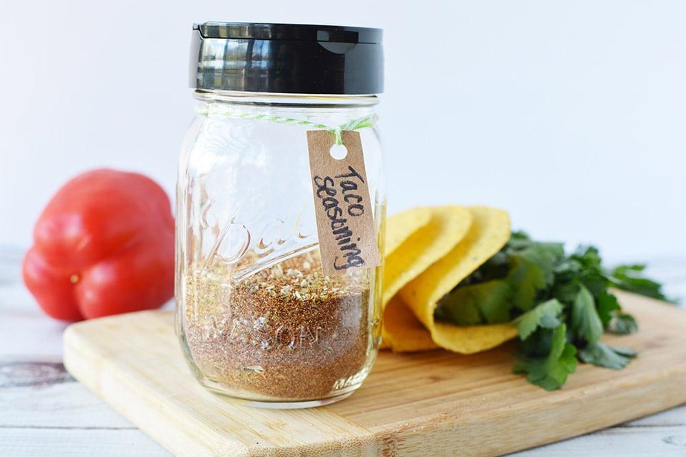 jar of homemade taco seasoning mix on a board