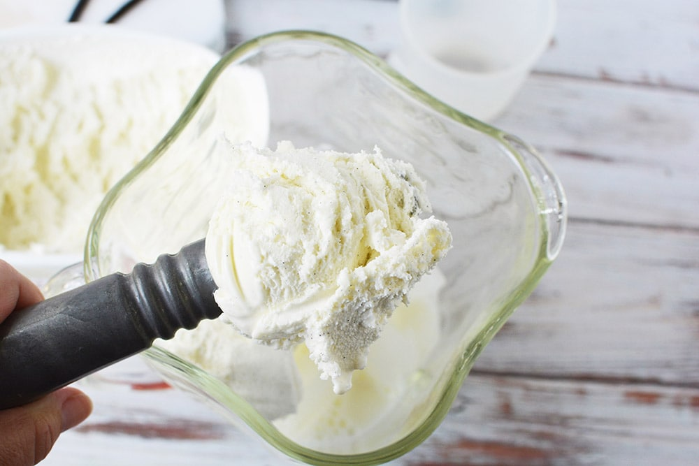 scooping vanilla bean ice cream into a blender