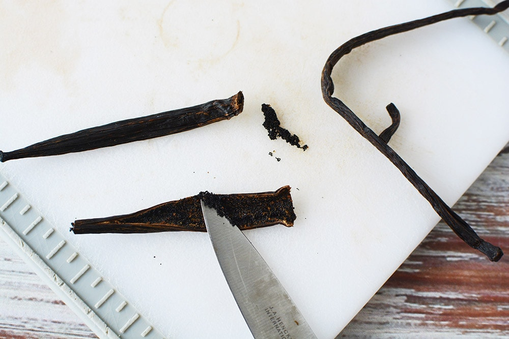scooping out vanilla beans with a knife on a cutting board