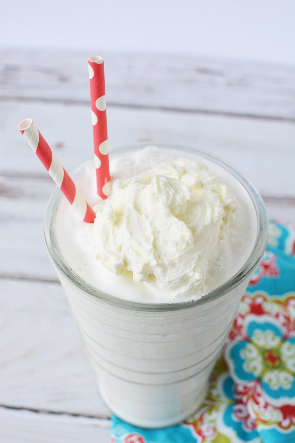 blended vanilla bean frappe in a glass with two red straws