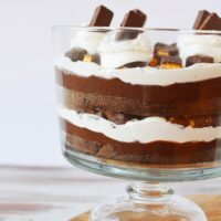 chocolate trifle with layers of pudding, whipped cream, and cake in a bowl
