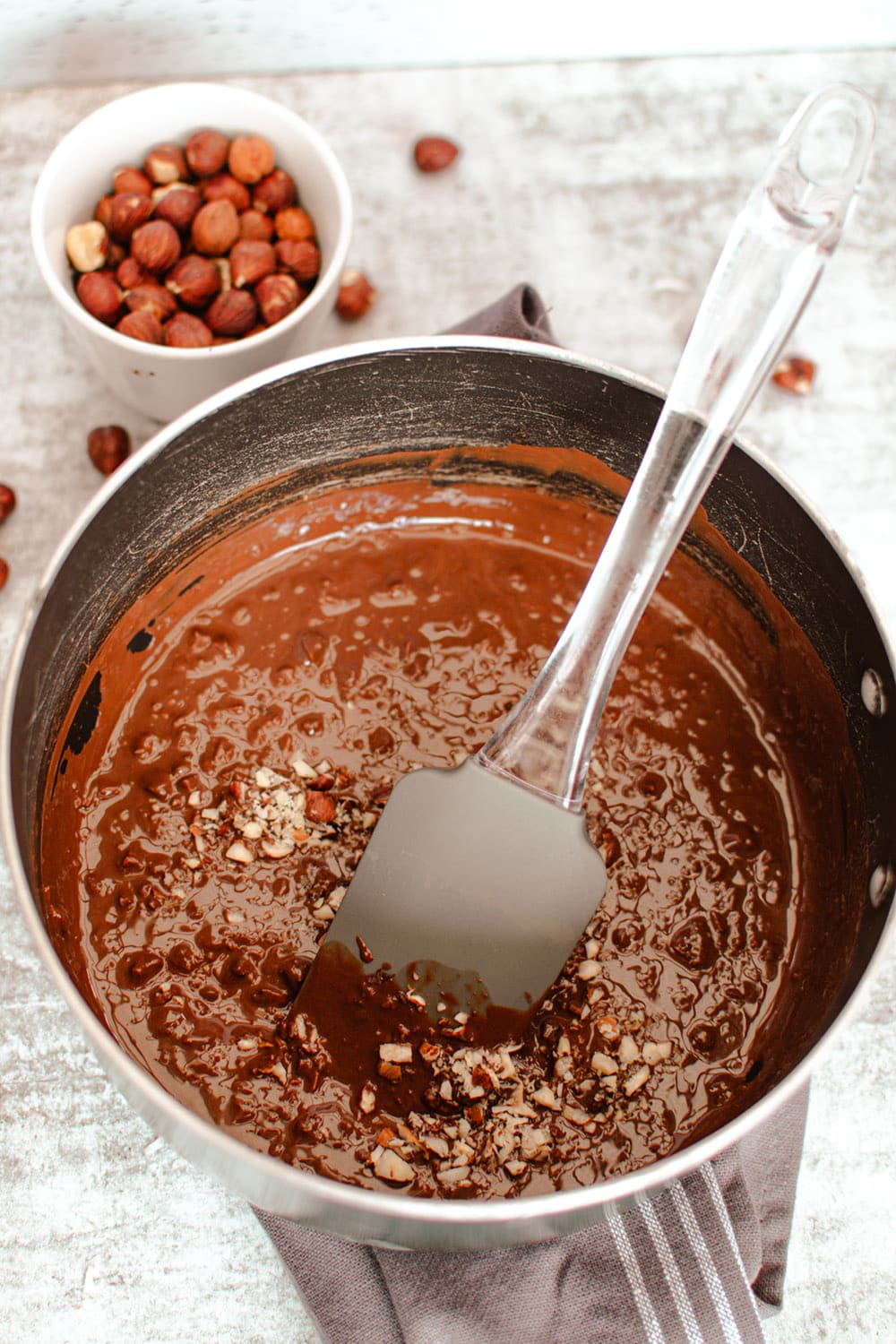 stirring melted chocolate and coconut in a pan