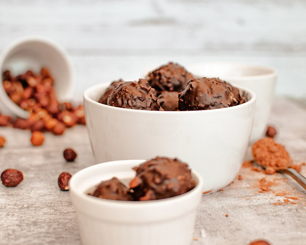 date balls in a bowl with hazelnuts and other ingredients