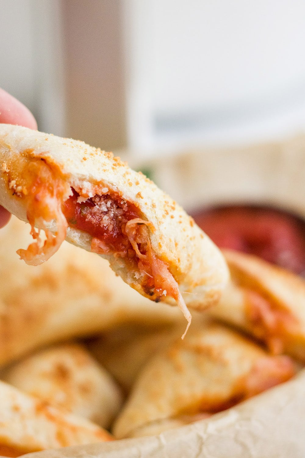 bite out of a pizza roll showing sauce and cheese