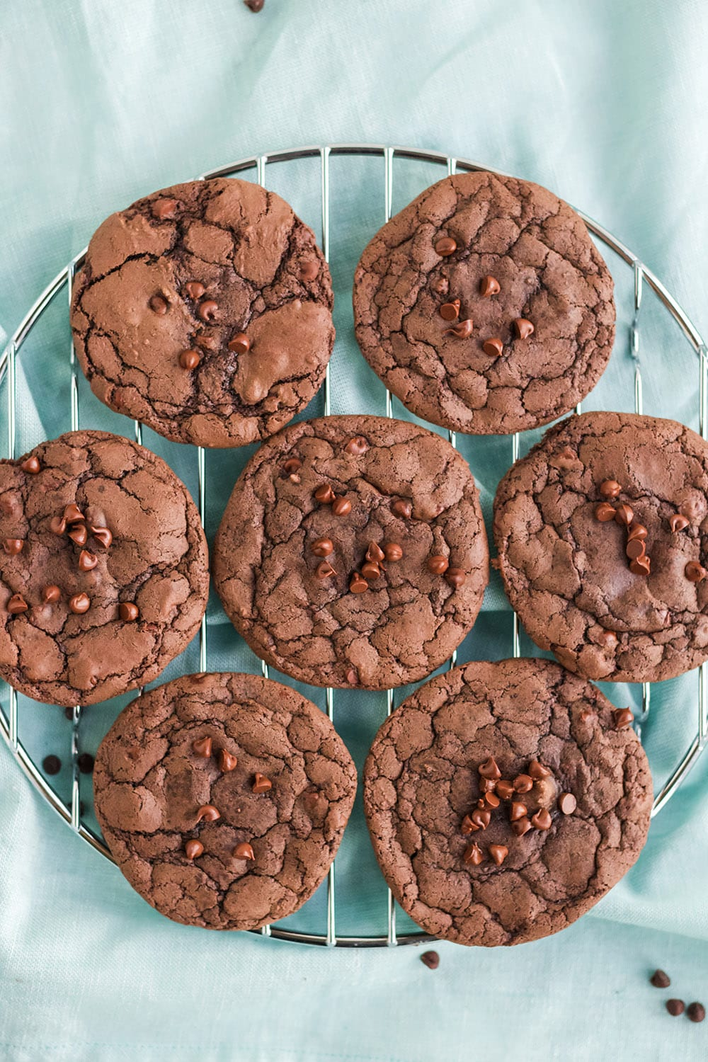 Brownie mix cookies on a rack on a blue towel.