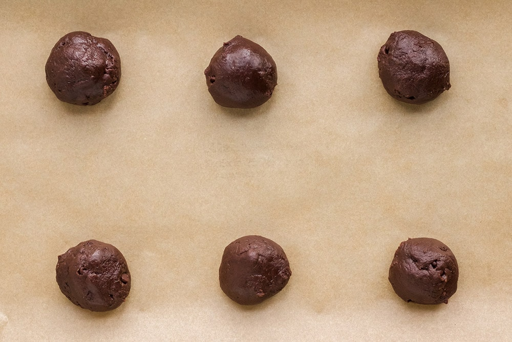 Balls of brownie mix dough on a cookie sheet.