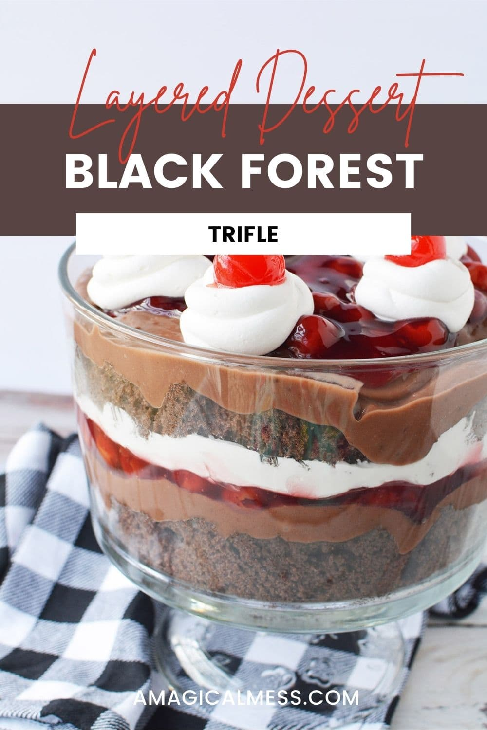 Layers of cake, whipped cream, and cherries in a trifle bowl.