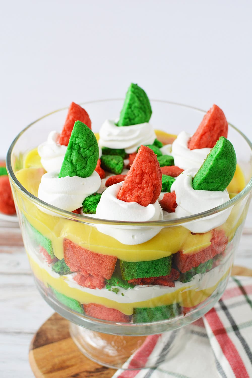 Christmas dessert trifle on a table with red and green cake and cookies.