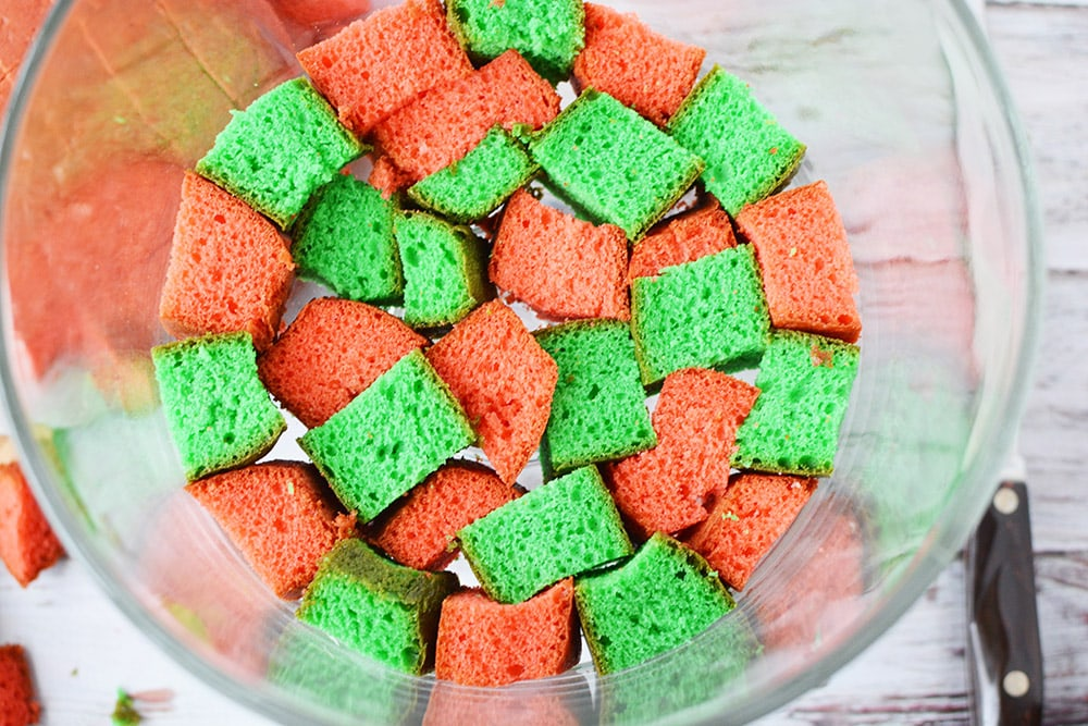 Cubes of red and green cake in a trifle bowl.