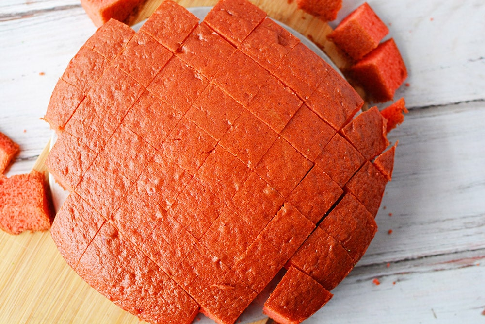 Red round cake sliced into square cubes