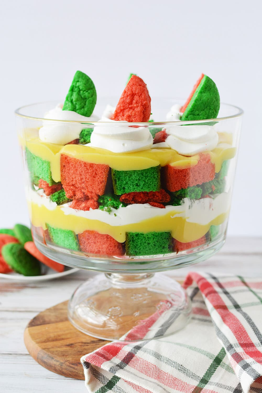 Layers of red and green cake, cookies, whipped cream, and pudding in a trifle dish.