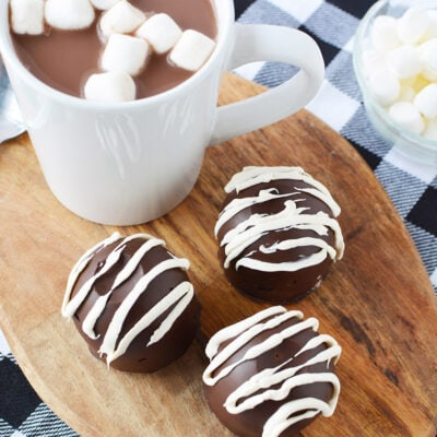 Three hot chocolate bombs on a board next to a mug.