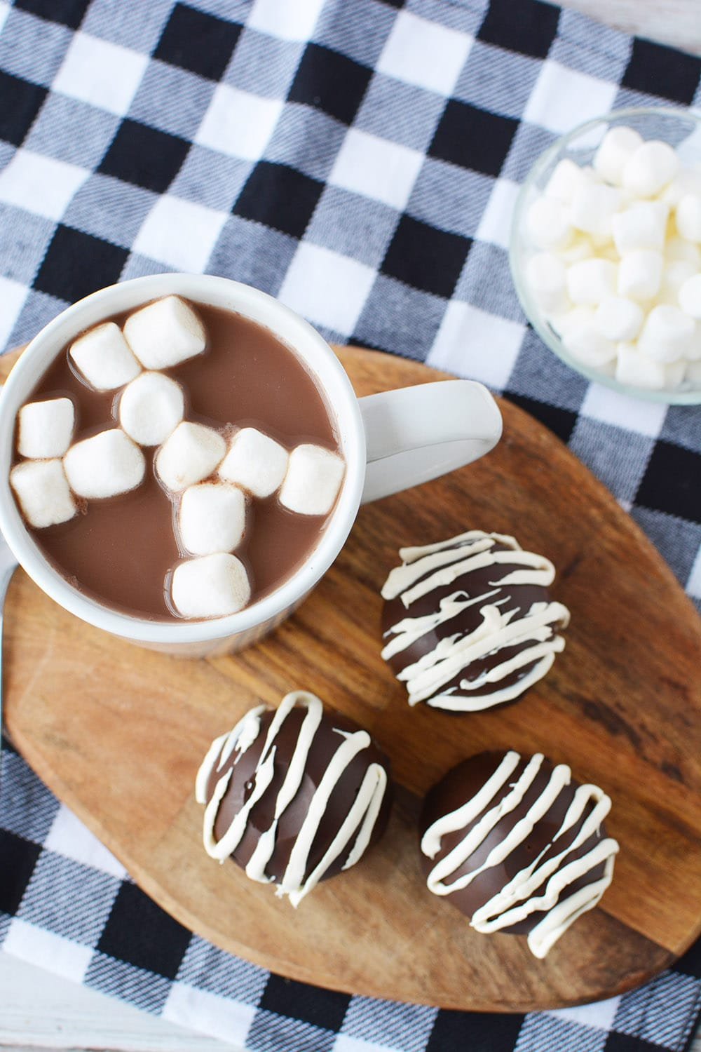 Three hot chocolate bombs next to a mug of hot chocolate with marshmallows in a bowl and a blue checked napkin.