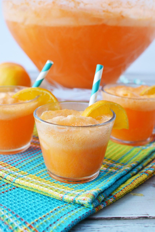 Glasses of orange punch around bowl.