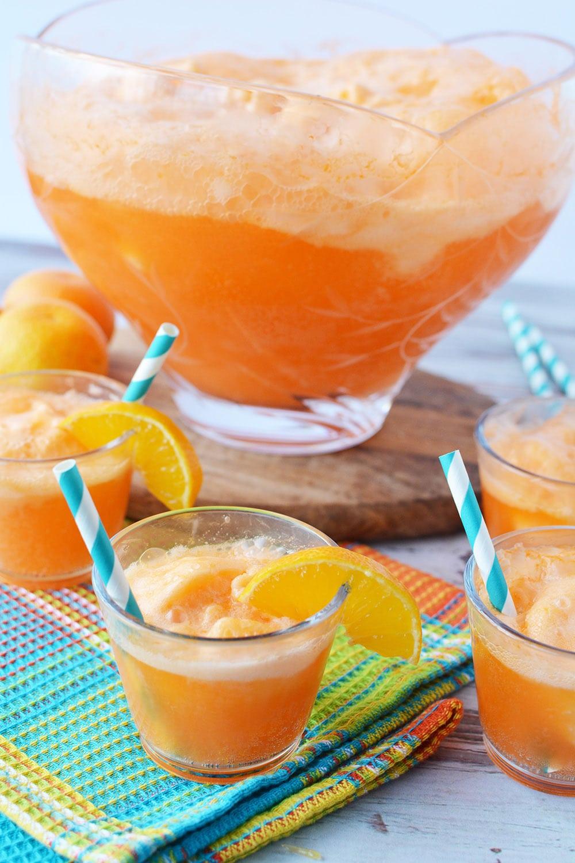 Cups full of orange sherbet punch around bowl.