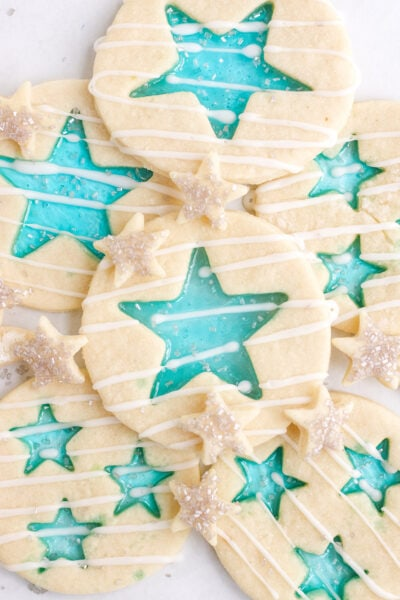 Stained-glass candy cookies with blue stars in different sizes on a white plate.