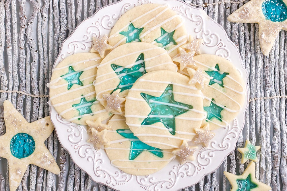 Stained-glass cookies with blue stars on a white plate on a gray table.