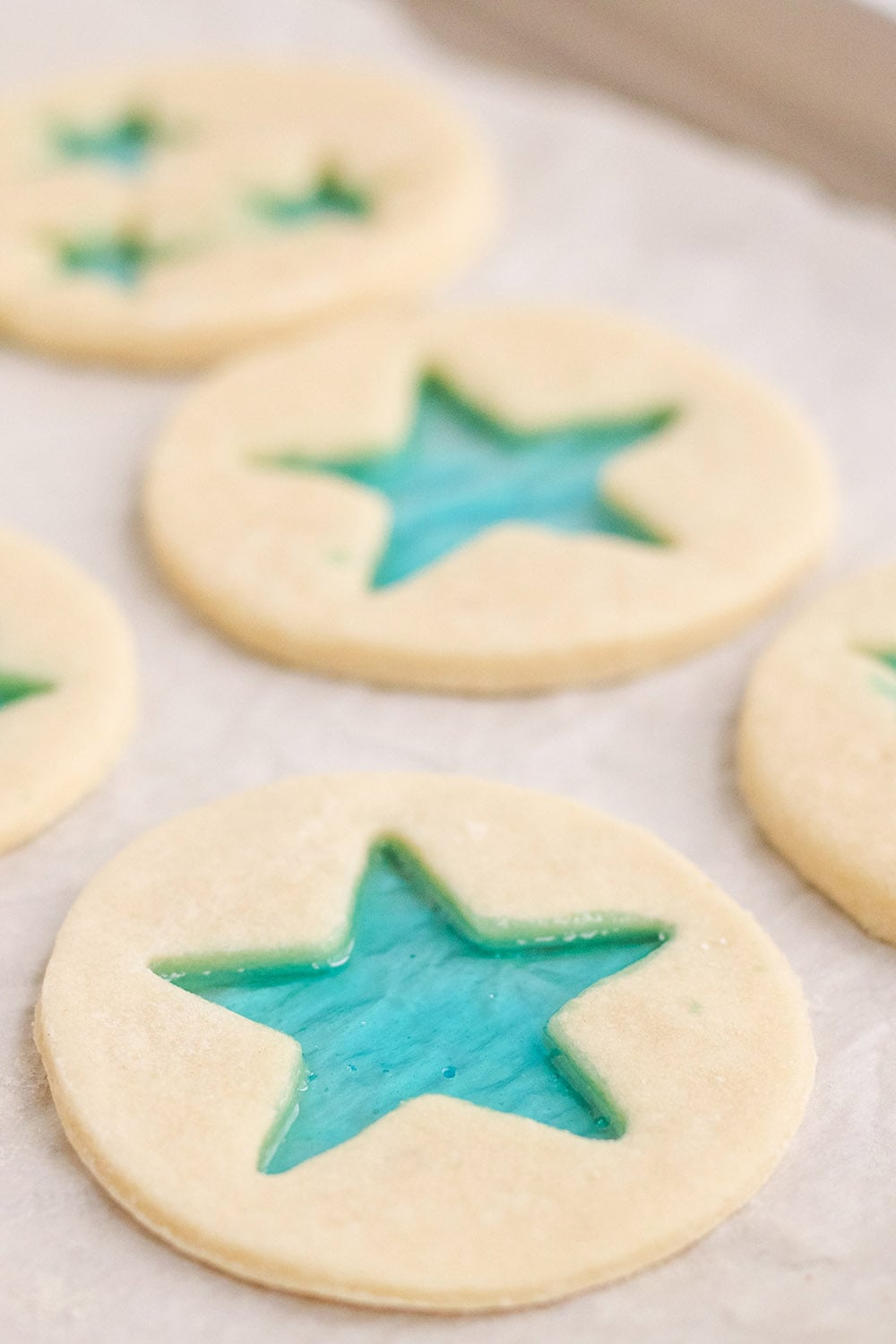 Stained-glass star cookies ready to bake on a baking sheet.