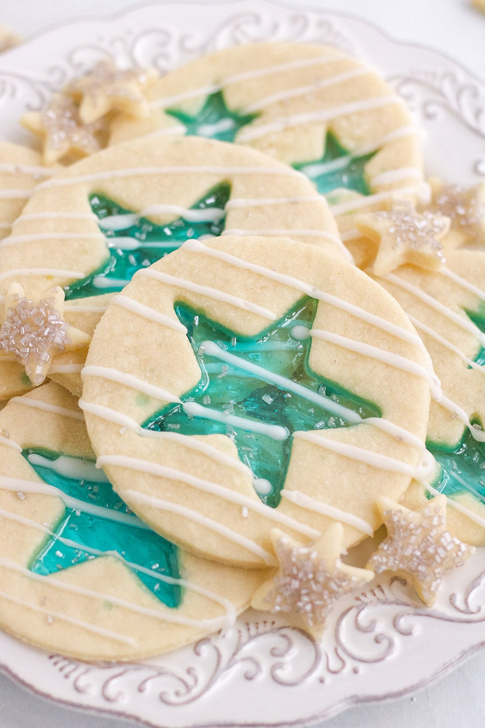 Stained-Glass blue star cookies on a white plate.