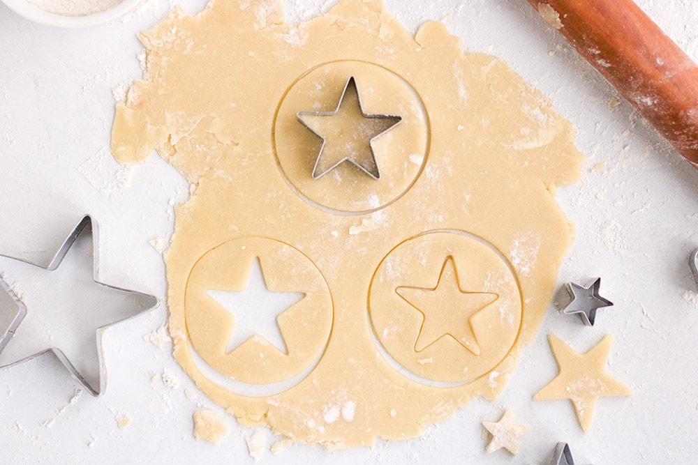 Cutting star shapes into cookie dough.
