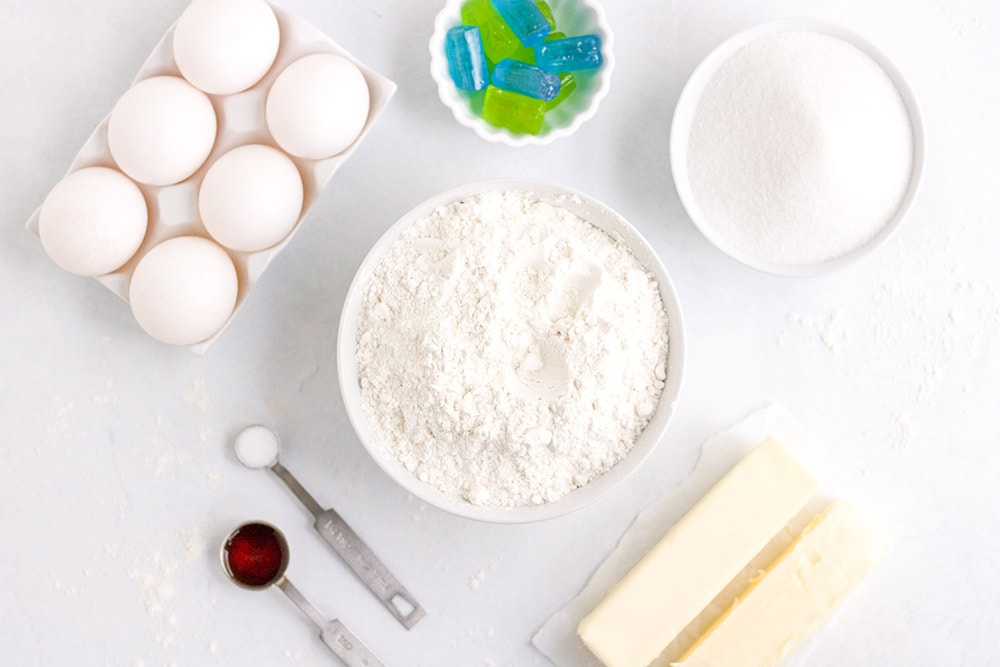 Eggs, flour, butter, vanilla, and candies for stained-glass cookies on a table.