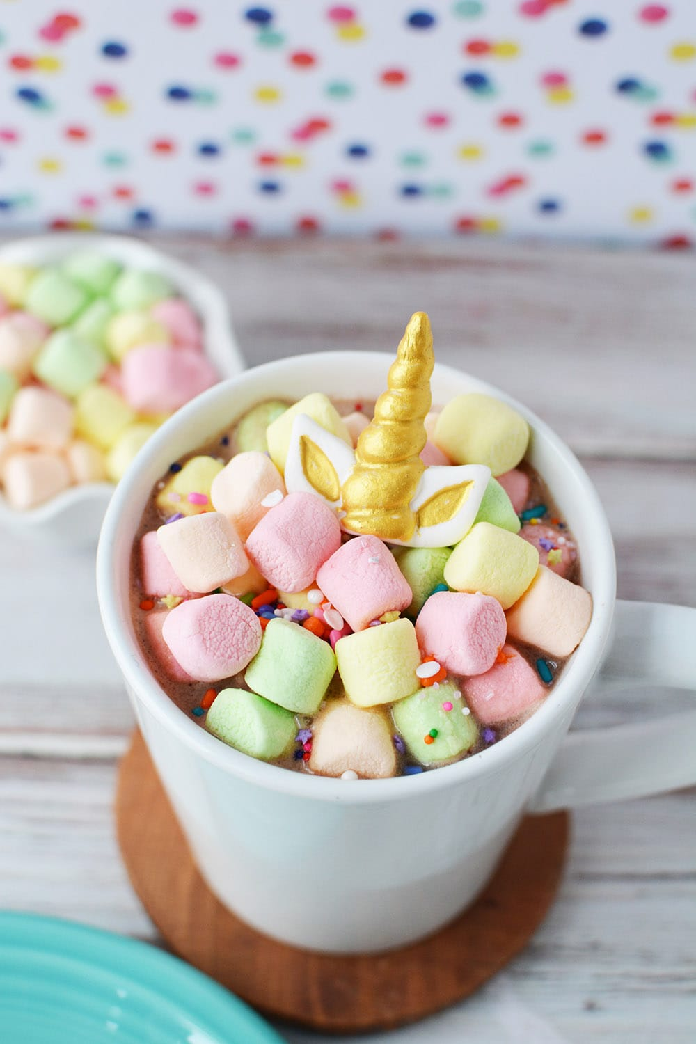 Hot chocolate in a mug topped with colored marshmallows and a gold unicorn horn.