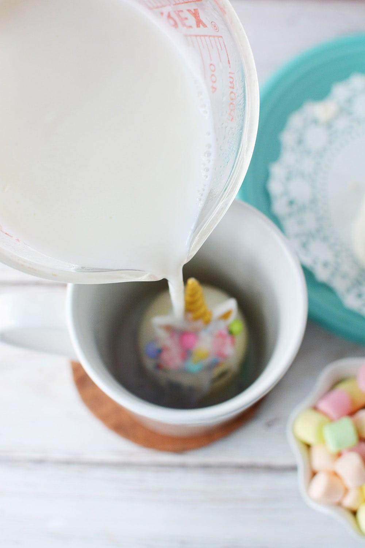 Pouring hot milk onto unicorn hot chocolate bomb in mug.
