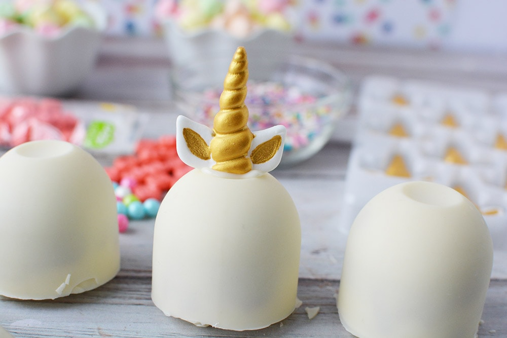White unicorn hot chocolate bomb with gold horn and ears.