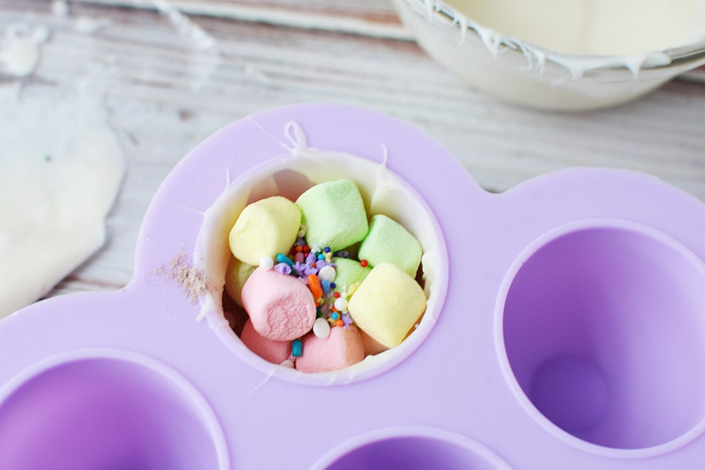 Colored marshmallows and sprinkles in hot chocolate bomb mold.