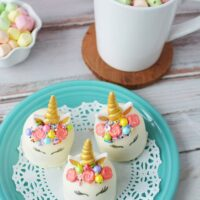 Unicorn hot chocolate bombs on a blue plate buy finished hot chocolate with colored marshmallows.