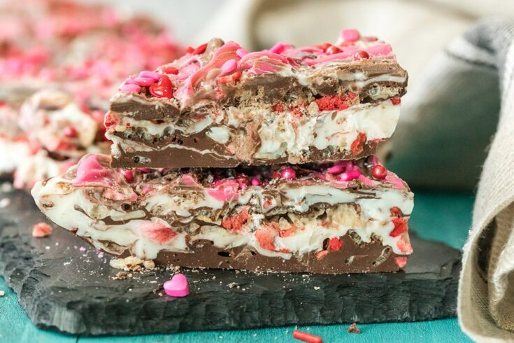 Pieces of strawberry chocolate bark candy stacked on a board.
