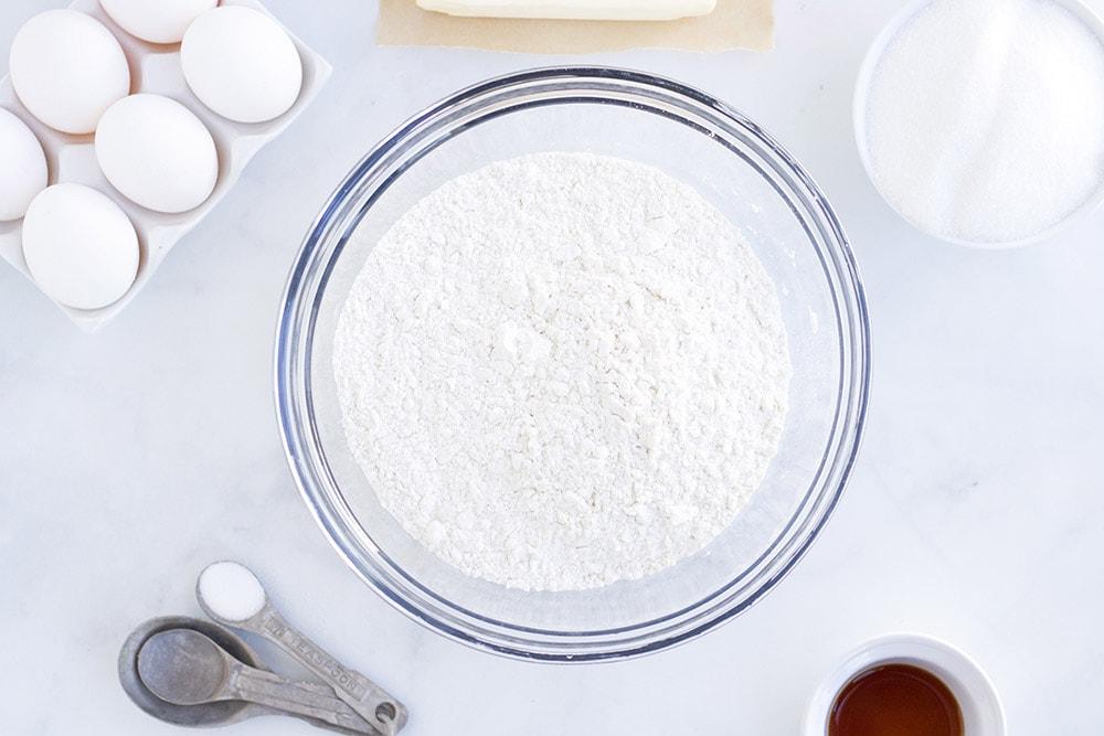 Bowl of sugar, eggs, and other sugar cookie ingredients.