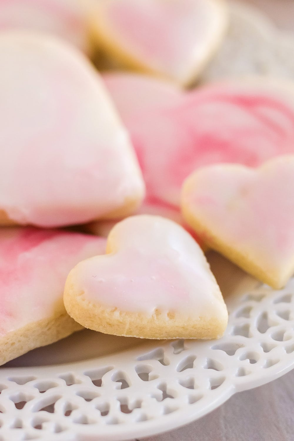 Plate of sugar cookies shaped into hearts with pink and white marble icing.