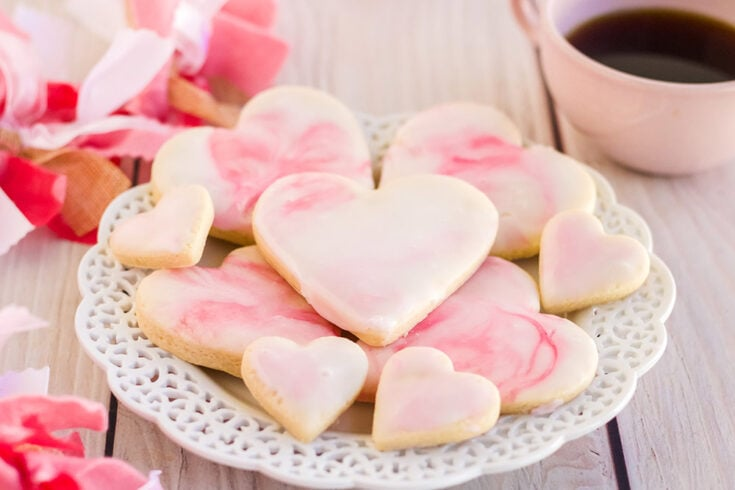 Heart cookies with marble icing with pin decorations on the table.