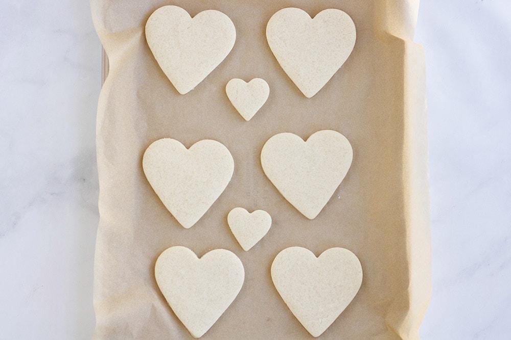 Baked heart shaped sugar cookies on pan.
