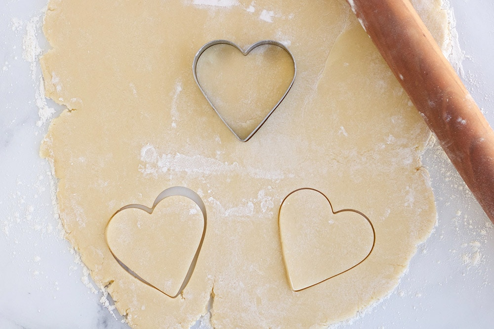 Cutting hearts out of sugar cookie dough with heart cookie cutter.