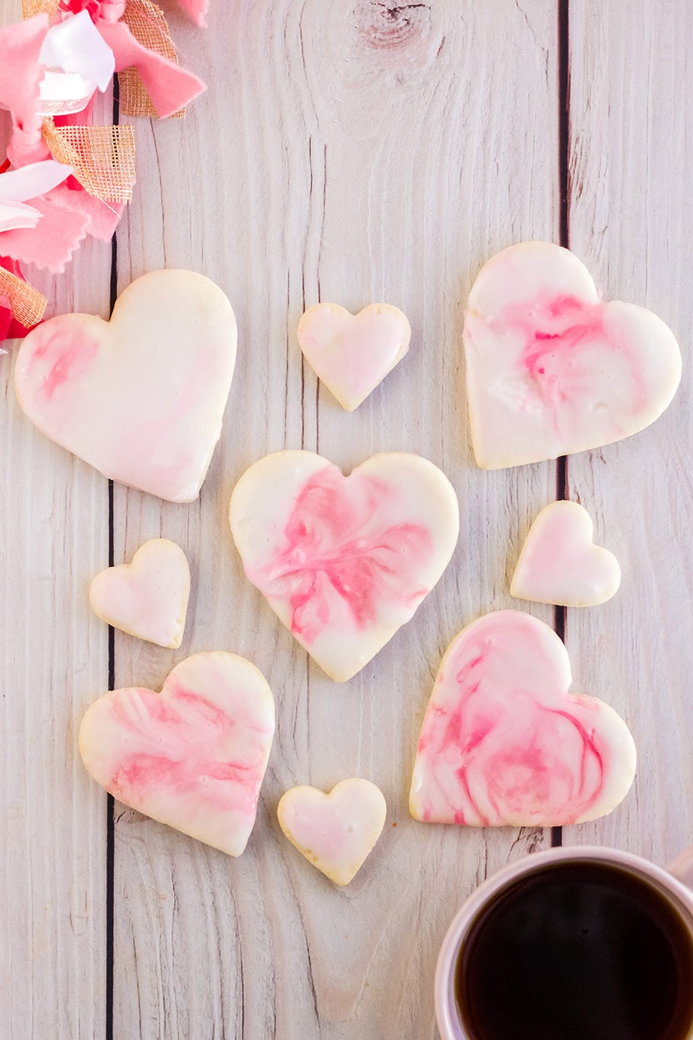 Valentine sugar cookies with pink icing on a board.