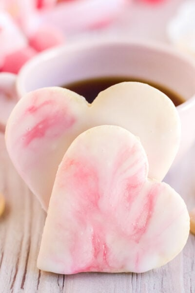 Two Valentine's day cookies in front of a cup of coffee.