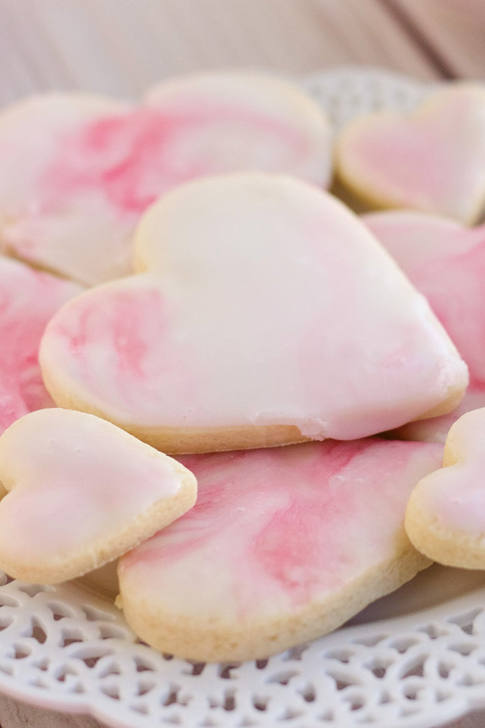 Pile of heart cookies with pink icing on a plate.