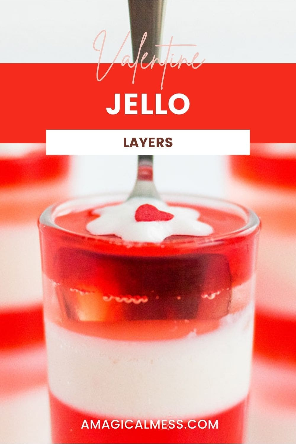 A spoon in a glass of layered jello topped with a tiny bit of whipped cream.