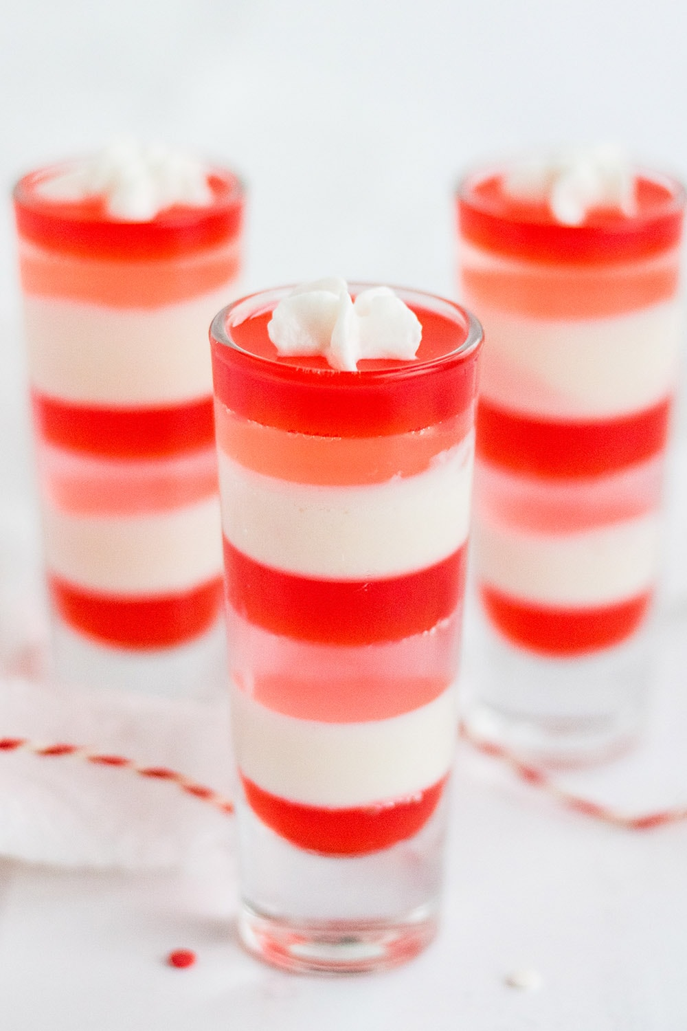 Three shooter glasses with layers of white, pink, and red jello.