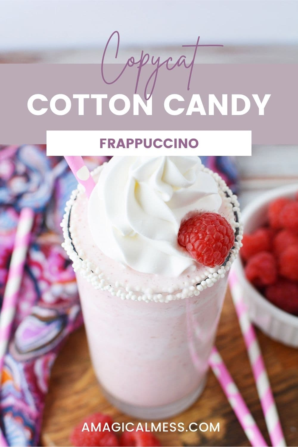 Cotton candy frapp with whipped cream and raspberries on a table.