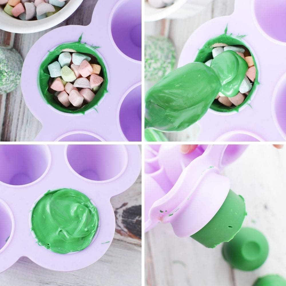 Filling mold with marshmallows and sealing it with green chocolate for cocoa bombs.