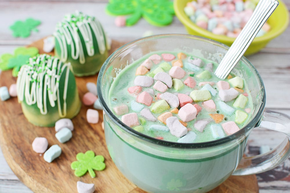 Mug of green hot chocolate with rainbow marshmallows sitting on a board next to green hot chocolate bombs and more marshmallows.