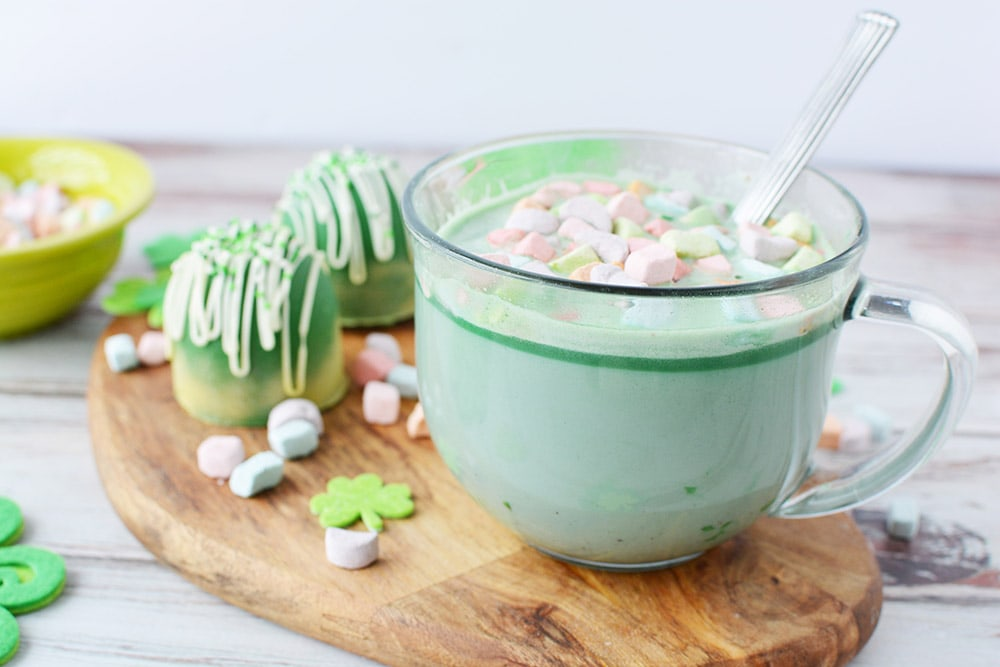 Clear mug with green hot cocoa topped with rainbow marshmallows sitting on a board next to hot cocoa bombs.