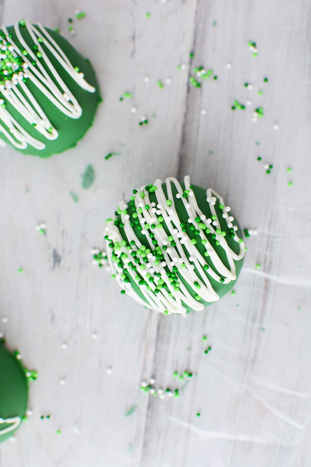 Topping a green hot chocolate bomb with St. Patrick's Day sprinkles.