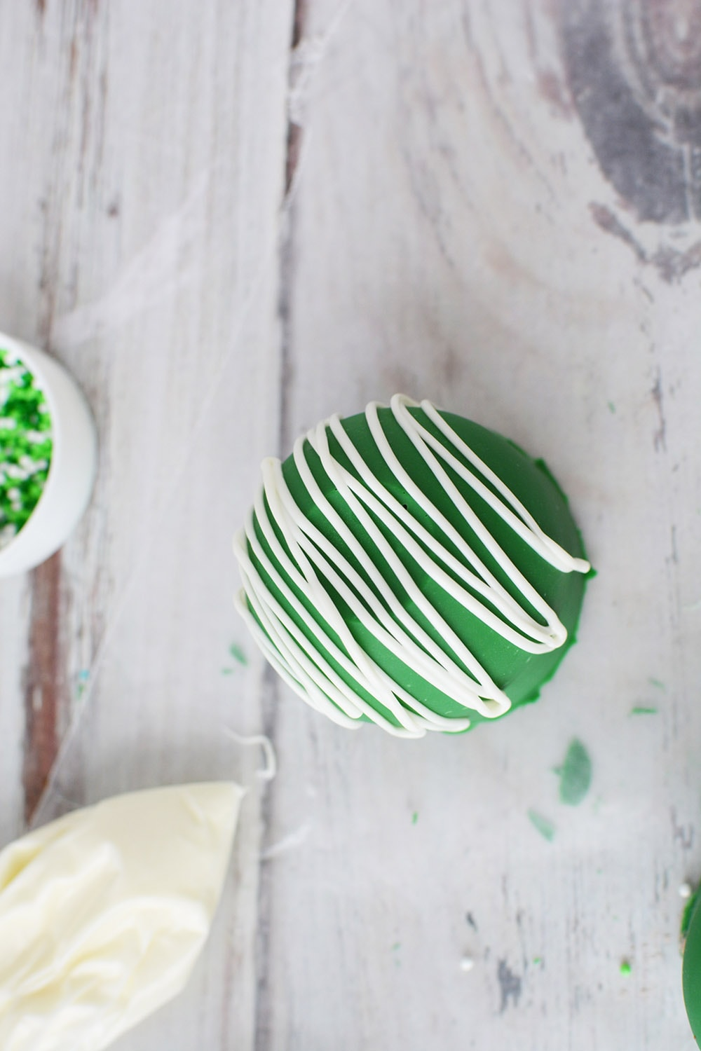 Green cocoa bomb on waxed paper to drizzle white candy topping.